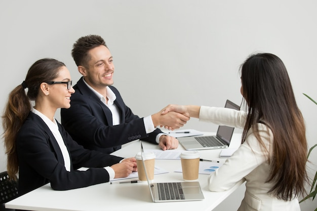 Friendly partners handshaking at group meeting thanking for successful teamwork Free Photo