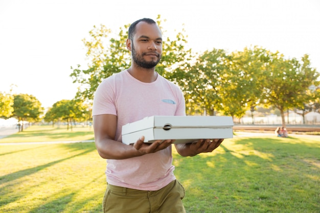 Friendly positive restaurant courier carrying pizza Free Photo