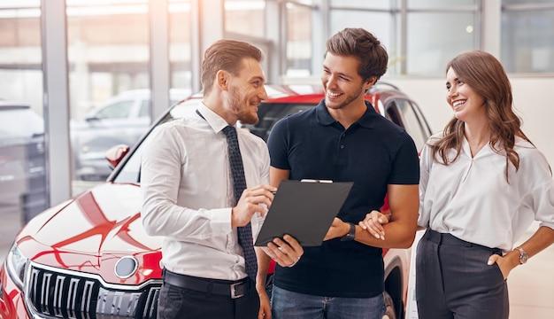 자동차 대리점에서 차량을 판매하는 동안 행복한 남자와 여자에게 계약을 보여주는 클립 보드와 친절한 세일즈맨 프리미엄 사진