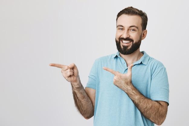 Uomo barbuto sorridente amichevole che indica le dita a sinistra Foto Gratuite