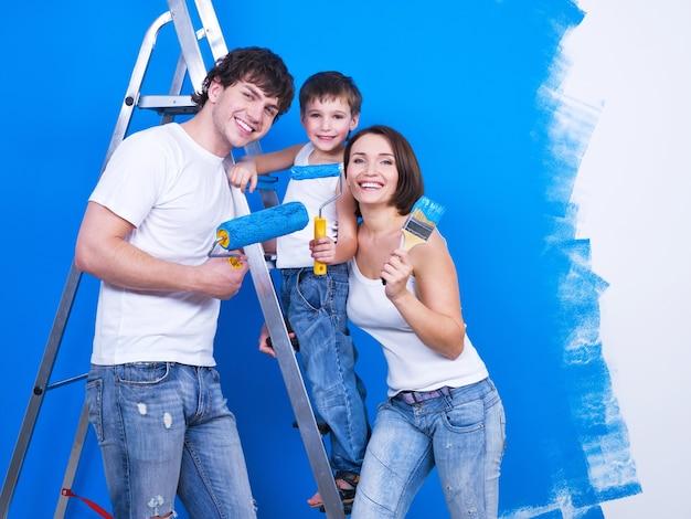 Famiglia sorridente amichevole con il giovane figlio che dipinge il muro Foto Gratuite