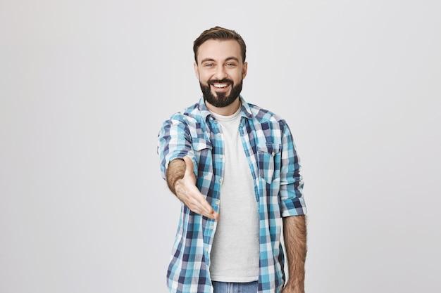 フレンドリーな笑みを浮かべて男は握手、挨拶のジェスチャーのために手を伸ばす 無料写真
