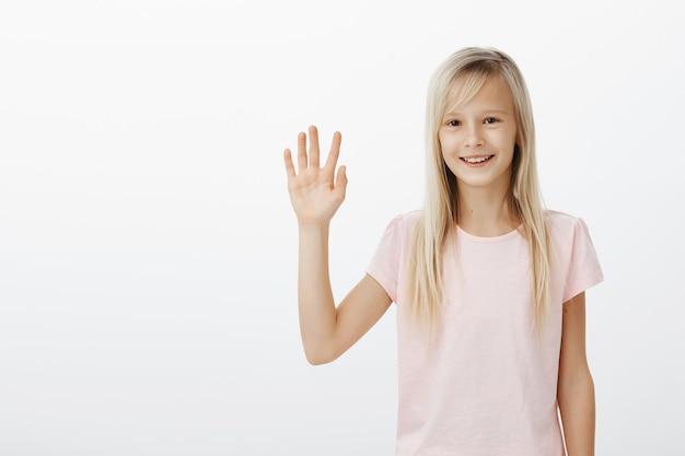 Ragazzo sorridente amichevole che dice ciao, piccola mano d'ondeggiamento della donna saluta Foto Gratuite