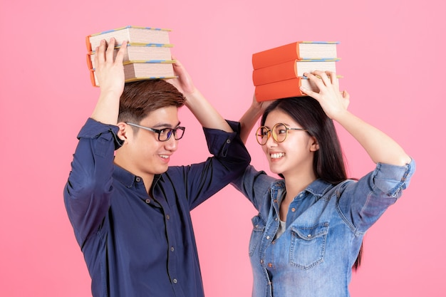 Friendly teenage man and woman place stack books on head Free Photo