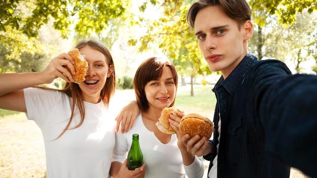 ハンバーガーとビールを飲みながら自分撮りをしている公園の友達 無料写真