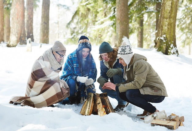 Friends camping in winter forest Free Photo
