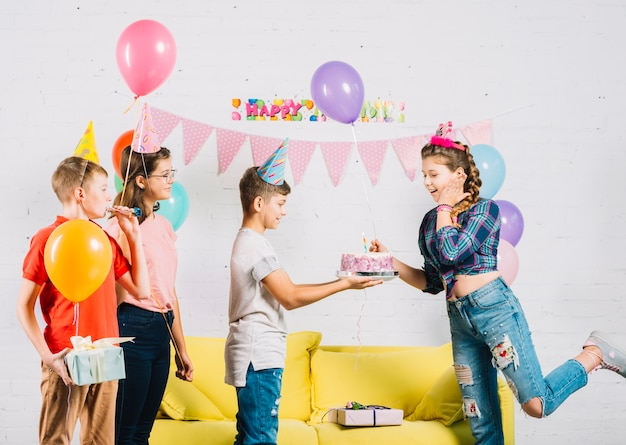Friends celebrating girl's birthday with cake Free Photo
