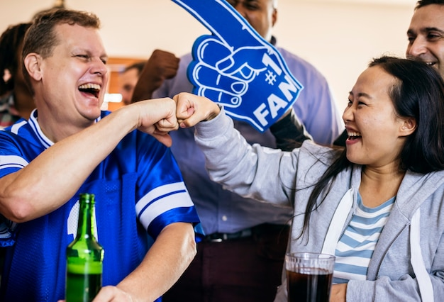 Friends cheering sport at bar together Free Photo