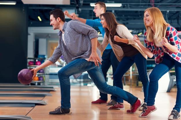 Amici che incoraggiano il loro amico mentre lanciano la palla da bowling Foto Gratuite