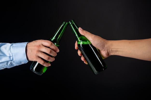 Friends clinking bottles of beer Free Photo