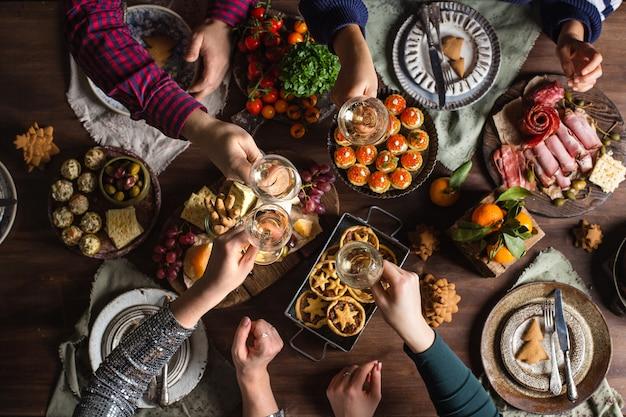 クリスマスディナーのために飲み物とグラスをチリンと鳴らす友人 Premium写真
