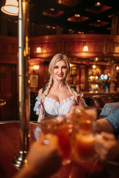 Друзья звенят кружками в пивном баре, официантка у стойки Premium Фотографии