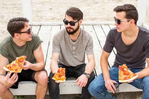 Friends conversing while sitting with pizza on beach Free Photo