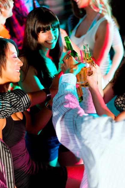 Friends dancing in club or disco Premium Photo