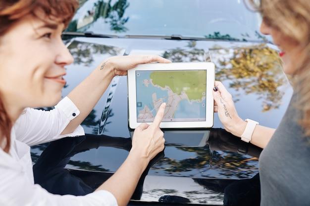 タブレット上の地図を議論する友人 Premium写真