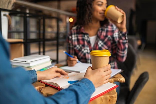Друзья вместе делают домашнее задание за чашкой кофе Premium Фотографии