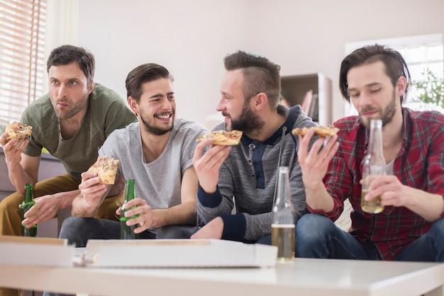 맥주를 마시고 피자를 먹는 친구 무료 사진