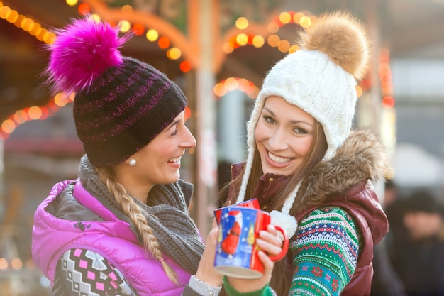 Friends drinking eggnog on christmas market Premium Photo