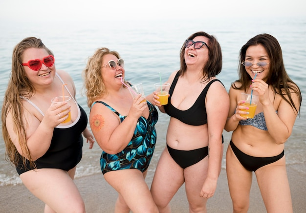 Friends drinking juice at the beach front view Free Photo