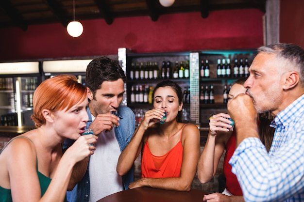 Friends drinking tequila at the table Premium Photo