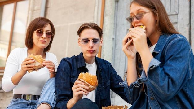 屋外でハンバーガーを食べる友達 無料写真
