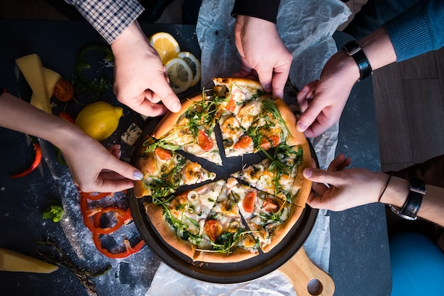 Friends eating pizza. people's hands grabbing a slice of pizza Premium Photo