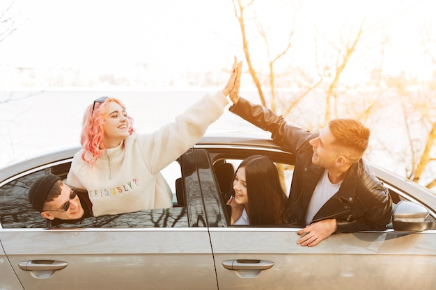 Friends giving high five from car window Free Photo