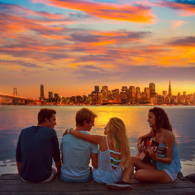 Friends group playing guitar in sunset pier at dusk Premium Photo