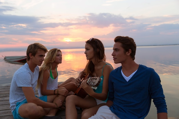 Friends group at sunset beach having fun with guitar Premium Photo