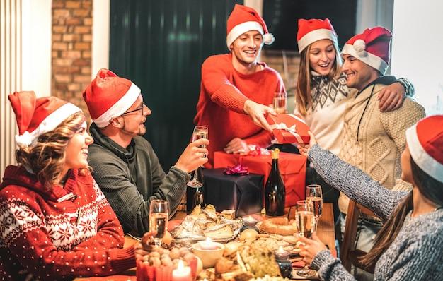 Группа друзей в шляпе санта-клауса дарит друг другу рождественские подарки Premium Фотографии