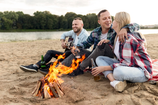 Friends hanging out at a campfire Free Photo