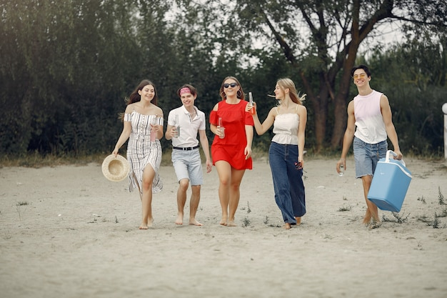 Friends have fun on a beach with drinks Free Photo