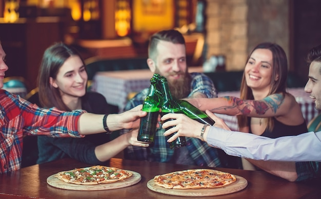 Friends having a drinks in a bar, they are sitting at a wooden table with beers and pizza. Premium Photo