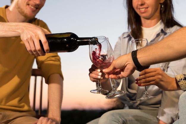夕暮れ時に屋外でワインを飲んでいる友達 Premium写真