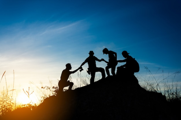 Friends helping each other and with teamwork trying to reach the top of the mountains Premium Photo
