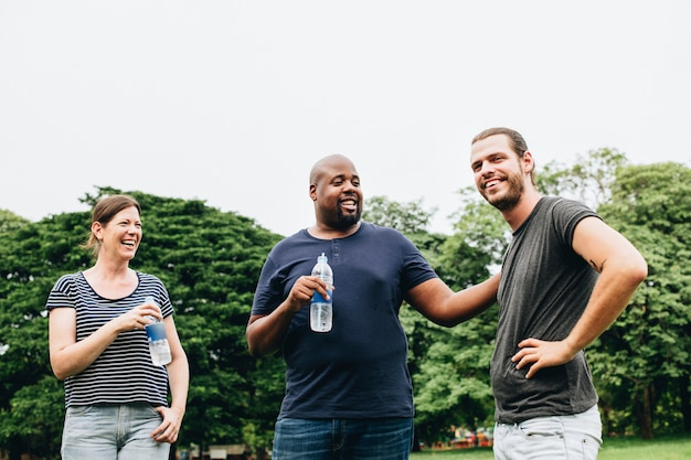 Friends holding a bottle of water and chatting in the park Premium Photo