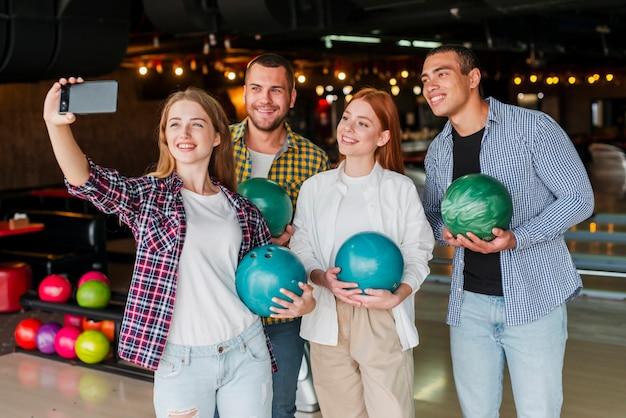 Amici che tengono le palle da bowling colorate Foto Gratuite