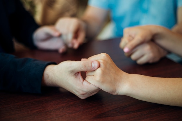 Friends holding each other hands sitting at table Premium Photo