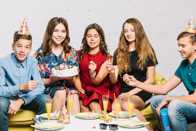 Friends holding fire crackers in hand sitting with birthday girl holding cake in hand Free Photo