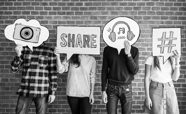 Friends holding up thought bubbles with social media concept icons Free Photo