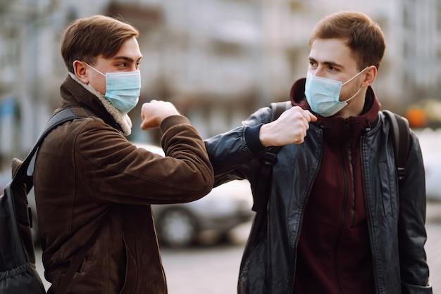 Друзья в защитной медицинской маске на лице приветствуют свои локти Premium Фотографии