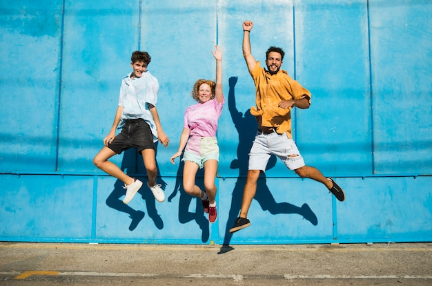 Friends jumping with blue wall behind Free Photo