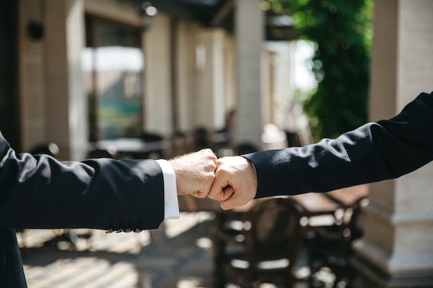 Friends knock hands at the wedding ceremony Free Photo