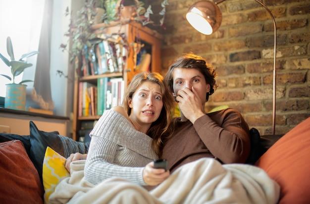 집에서 공포 영화를보고있는 친구-커플 Tv 시청, 소파에 앉아 담요 아래 껴안기 프리미엄 사진