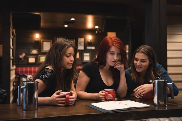 Друзья, глядя на меню в баре Бесплатные Фотографии