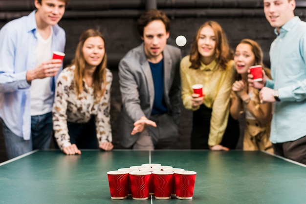 Friends looking at ball while man playing beer pong in bar Free Photo