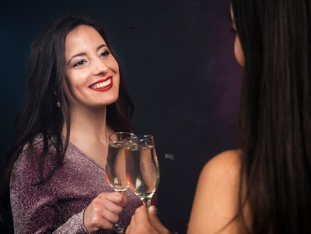 Friends looking at each other with champagne at new years party Free Photo