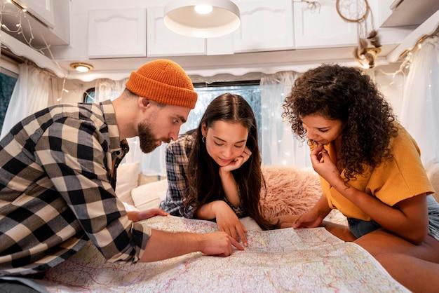 Друзья смотрят на карту в фургоне Бесплатные Фотографии