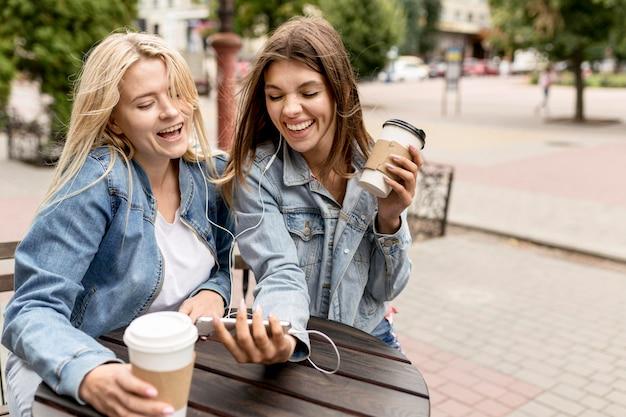 Друзья смотрят на телефон снаружи Бесплатные Фотографии
