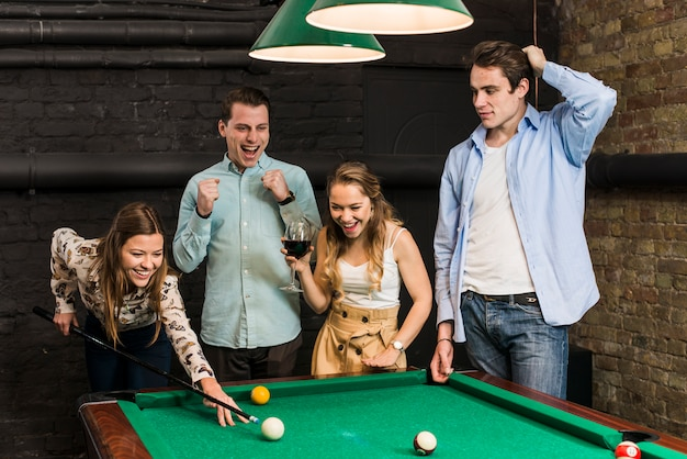 Friends looking at smiling woman playing snooker in club Free Photo